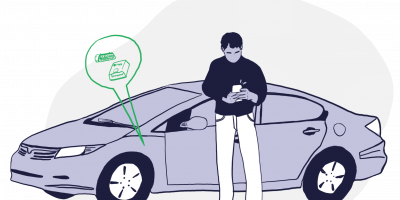 man in front of car looking at phone trying to find his obd2 port