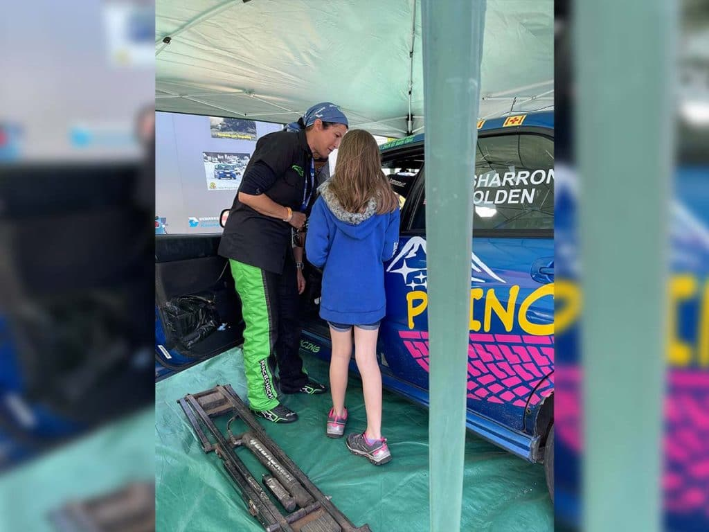 Margaret Sharron showing a young girl her race car